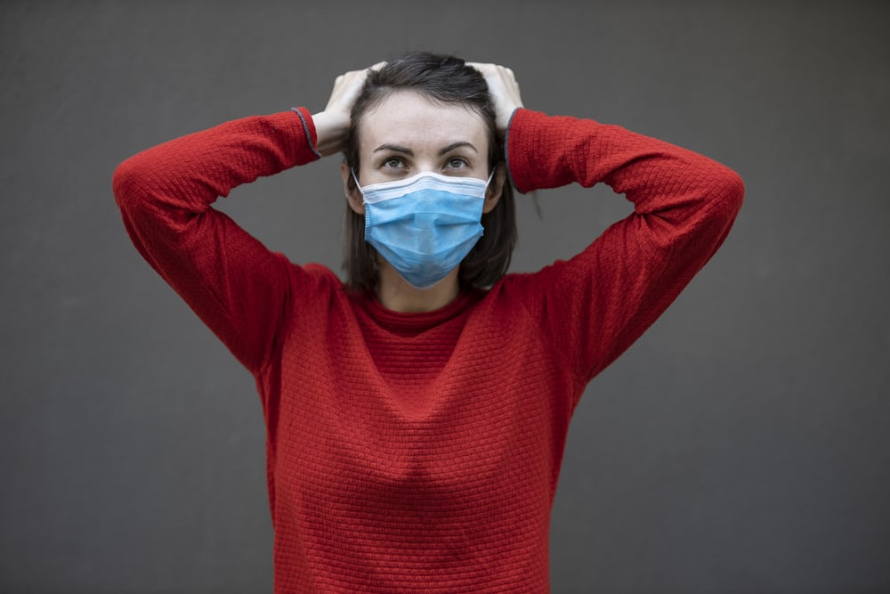 Frustrated person wearing mask with hands on their head